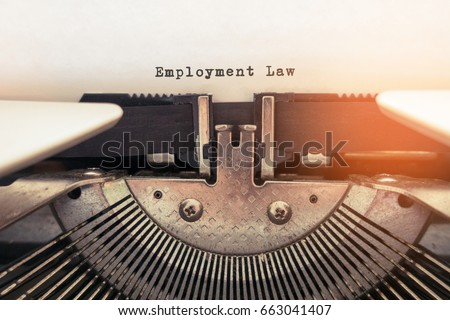 Employment Law word typed words on a vintage typewriter.  Selective focus and vintage tone color