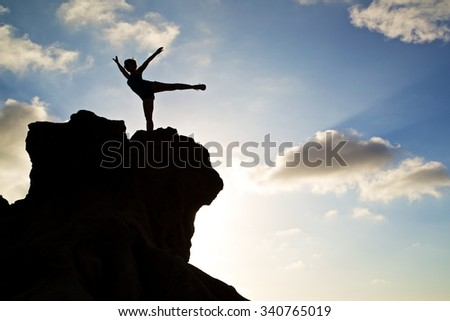 Empowered woman dancing on top of a cliff.