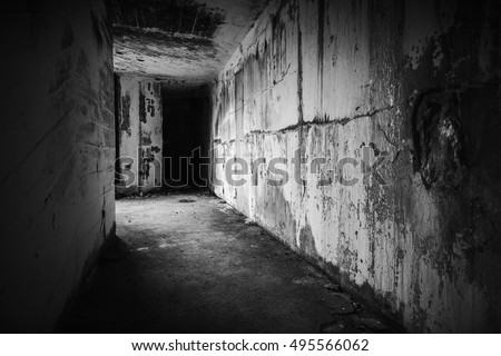 Empty abandoned bunker interior with dark end of grungy corridor, black and white photo