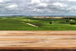 Empty aged harsh wooden table suface on a blurred countryside natural background for display and montage your products.