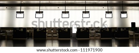 Empty airport interior with check-in and empty info monitors.