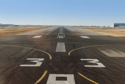 empty airport runway with white markings for aircraft