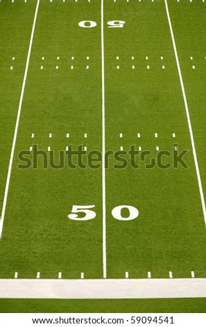 Empty American football field showing 50 yard line.