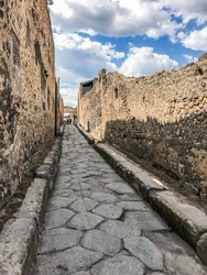 Empty Ancient Roman city of Pompeii under a blue sky with clouds. Panorama of an abandoned street in Pompeii. City ruins, cobbled road