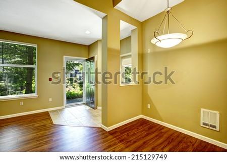 Empty apartment with open floor plan. Entrance hallway with open door and tile floor