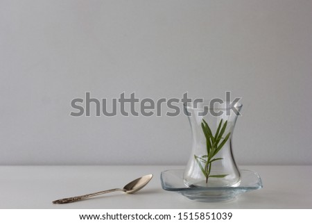 Empty Armudu tea glass with branch of rosemary in it and spoon on the table on the white background Photo stock ©