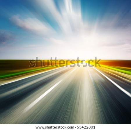 Empty asphalt blurry road with cloudy sky and sunlight - stock photo