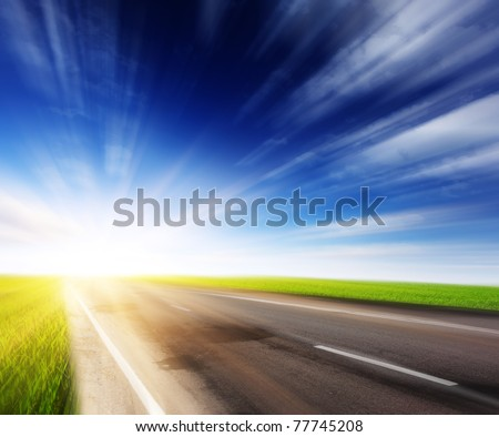 Empty asphalt blurry road with cloudy sky and sunlight
