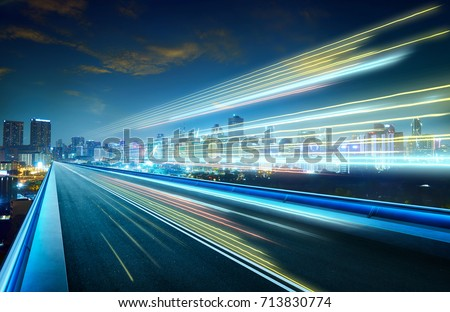 Empty asphalt flyover with city skyline and light trails ,night scene . #713830774