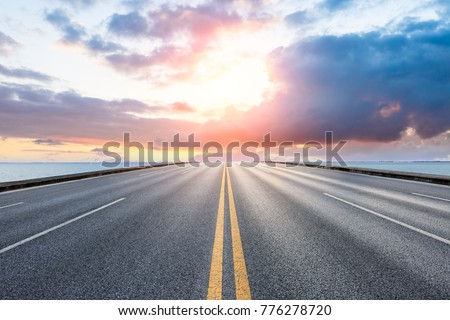empty asphalt highway and blue sea nature landscape at sunset
