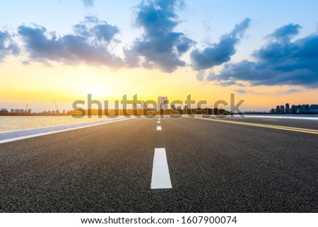 Empty asphalt highway and Suzhou city skyline with colorful sky at sunset.
