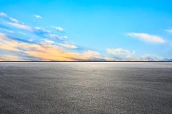Empty asphalt race track and sunset sky