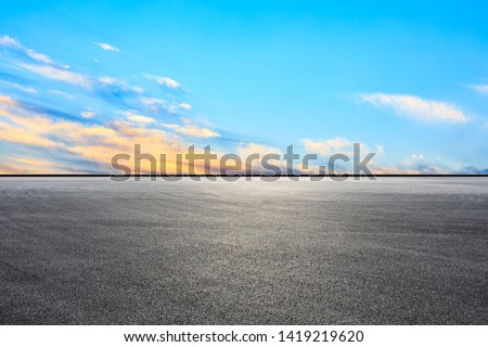 Empty asphalt race track and sunset sky #1419219620