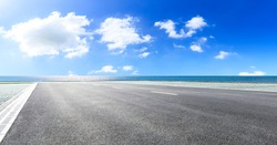 Empty asphalt road and blue sea with sky background