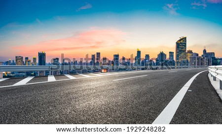 Empty asphalt road and city skyline with buildings at sunset in Shanghai.