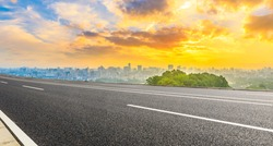 Empty asphalt road and city skyline with green mountain at sunrise in Hangzhou,China.