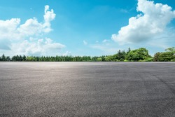 Empty asphalt road and green forest under blue sky.