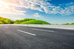 Empty asphalt road and green tea plantation nature landscape.