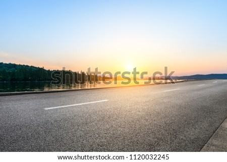 Empty asphalt road and hills silhouette at sunset #1120032245
