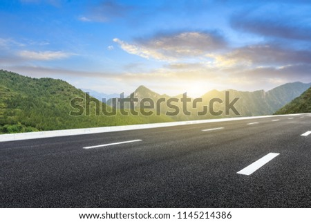 Empty asphalt road and mountains natural scenery at sunrise #1145214386