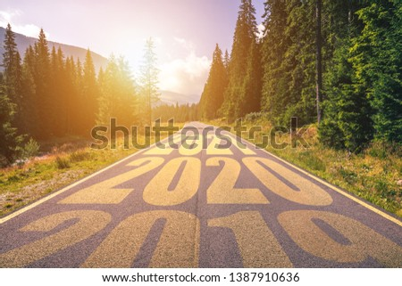 Empty asphalt road and New year 2019, 2020, 2021 concept. Driving on an empty road in the mountains to upcoming 2019, 2020, 2021 and leaving behind old years. Concept for success and passing time.