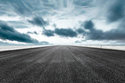 Empty asphalt road and sea on a blue typhoon day