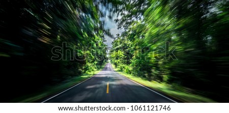 Empty asphalt road and speed motion blur on highway in summer with green trees forest at countryside #1061121746