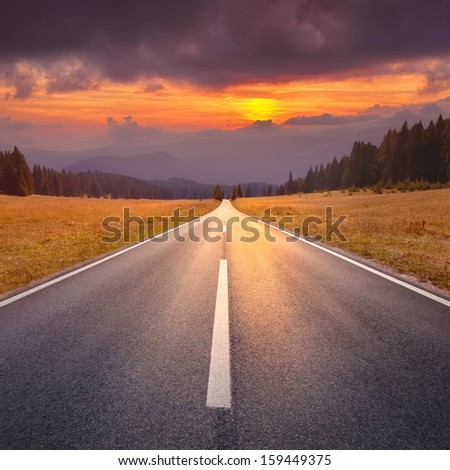 Empty asphalt road at sunset
