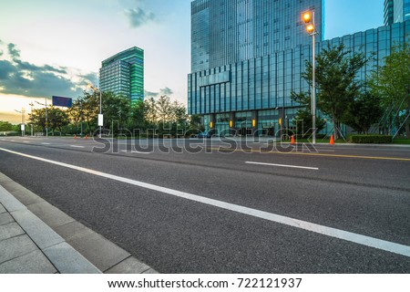 empty asphalt road front of modern buildings at dusk