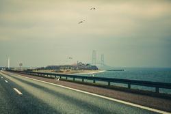 Empty asphalt road highway near the Baltic sea and bridge in the background to Denmark, grey moody dusk. Birds flying.