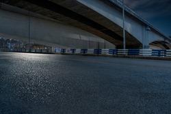 empty asphalt road in downtown under bridge at night.