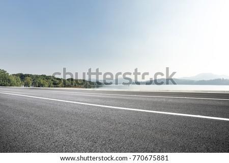 empty asphalt road near beautiful lake in blue sunny sky