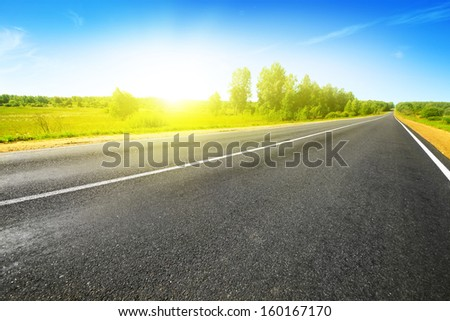 Empty asphalt road on bright summer day.