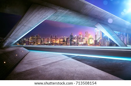 Empty asphalt road under the bridge during the night with beautiful city skyline background .