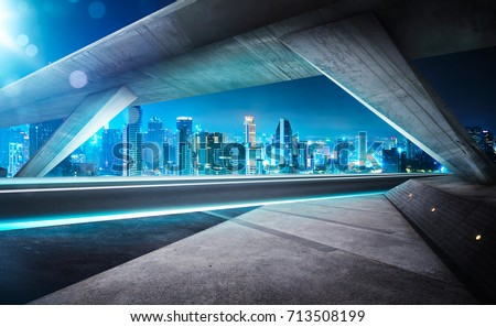 Empty asphalt road under the bridge during the night with beautiful city skyline background . #713508199