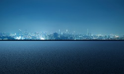 Empty asphalt road with city skyline background, night scene