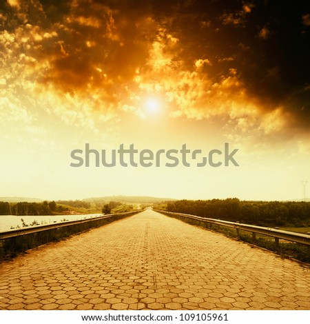 Empty asphalt road with cloudy sky and sunlight