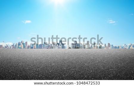 Empty asphalt road with modern city skyline background .