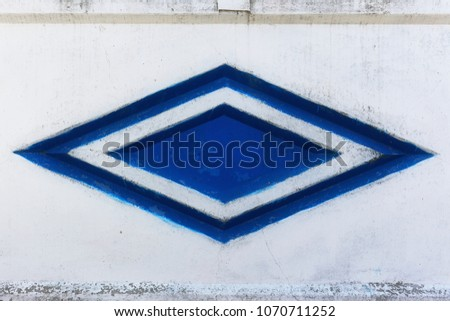 Empty background of a cement stone wall with notches of geometric shape. Abstract web banner. Texture of the rock fence facade with a blue rhombus in the middle. #1070711252
