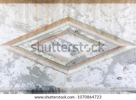 Empty background of a cement stone wall with notches of geometric shape. Abstract web banner. Texture of the rock fence facade with a rhombus in the middle. #1070864723