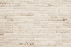 Empty background of wide cream brick wall texture. Beige old brown brick wall concrete or stone textured, wallpaper limestone abstract flooring. Grid uneven interior rock. Home decor design backdrop.