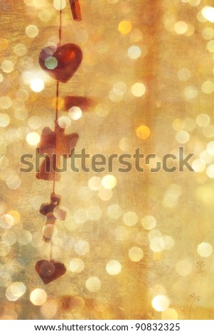 empty background with grunge texture and vintage garland of hearts and crosses with sparkling bokeh lights.