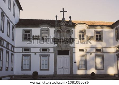 Empty backyard of ancient monastery in Europe. Facade of old building. Monastery exterior with cross on roof. Religious architecture. Monastery yard in sunlight in the morning. Close windows and door.