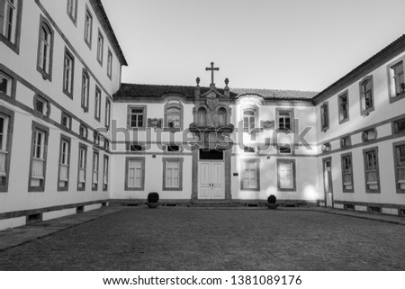 Empty backyard of ancient monastery in Europe monochrome. Facade of old building. Monastery exterior with cross on roof black and white. Religious architecture. Close windows and door.