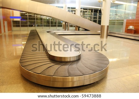 empty baggage carousel in airport hall with granite floor and glass walls