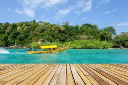 Empty bamboo table top with defocused yellow boat floating on turquoise water sea and tropical lush green island background for display or montage product.