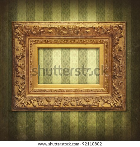 Empty baroque golden frame on Victorian floral green-gold stripe