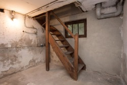 empty basement in abandoned old industrial building with little light and a wooden stairs darkness