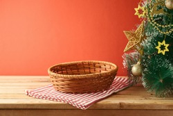 Empty basket on wooden table with tablecloth and Christmas tree with golden ornaments. Christmas background for mock up design