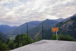 empty basketball court on the edge of a cliff in a mountain village in the Pyrenees, in the Aran Valley, Lerida Spain